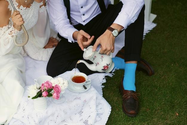 Noiva e noivo bebem chá com roupas brilhantes na grama verde