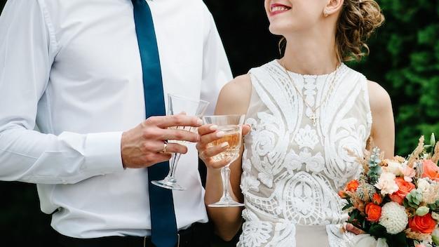 Noiva e noivo bebendo champanhe