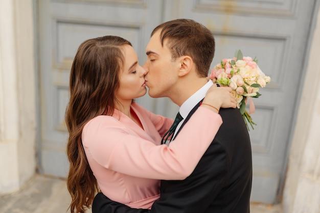 Noiva e noivo beijam perto da porta da igreja.