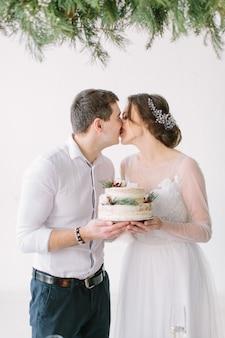 Noiva e noivo beijando à mesa no salão de banquetes do restaurante e segurando o bolo de casamento decorado com frutas e algodão