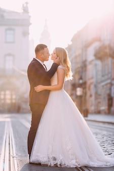 Noiva e noivo beijando na praça da cidade. perfil de recém-casados. praça da cidade com trilhos de bonde.