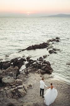 Noiva e noivo caminham em direção ao pôr do sol sobre o mar