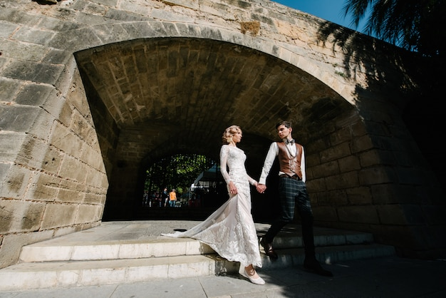 Noiva e noivo caminham juntos na cidade