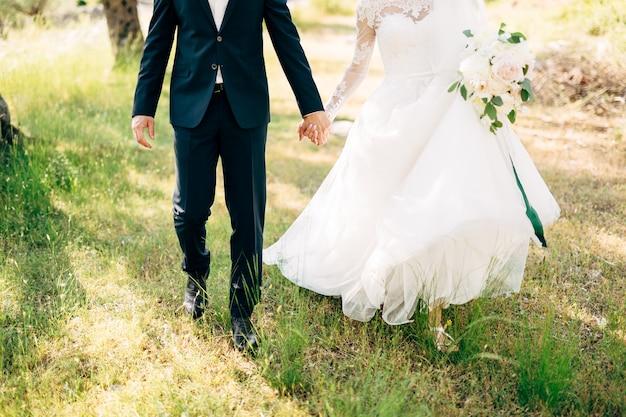 Noiva e noivo caminhando juntos em um olival de mãos dadas
