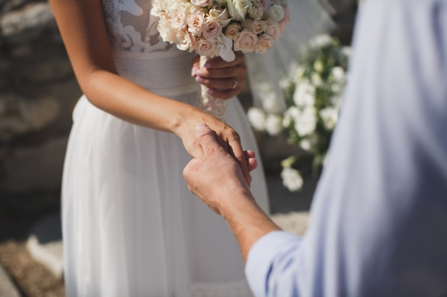 Noiva e noivo caminhando juntos, segurando suas mãos
