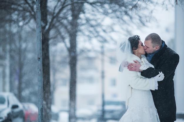 Noiva e noivo caminhando na cidade europeia na neve