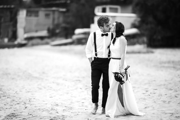 Noiva e noivo caminhando na praia, perto do mar e beijo. um lindo casal.