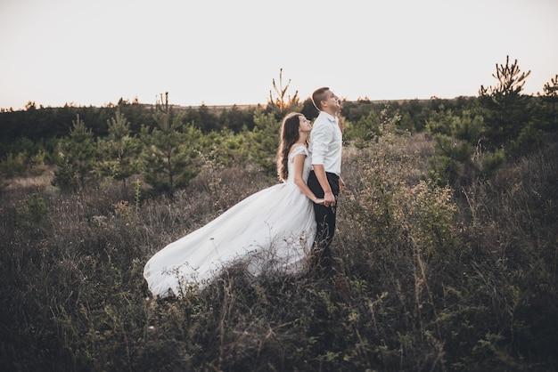 Noiva e noivo caminhando no prado
