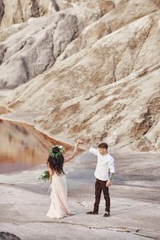 Noiva e noivo caminhar ao longo das montanhas vermelhas, cena fabulosa. casal apaixonado