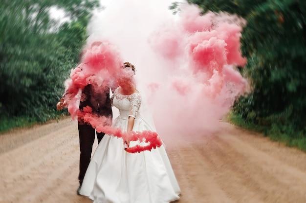 Noiva e noivo com a fumaça colorida vermelha no parque de verão