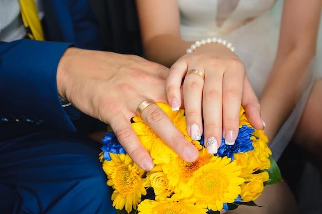 Noiva e noivo com alianças de casamento em um lindo buquê