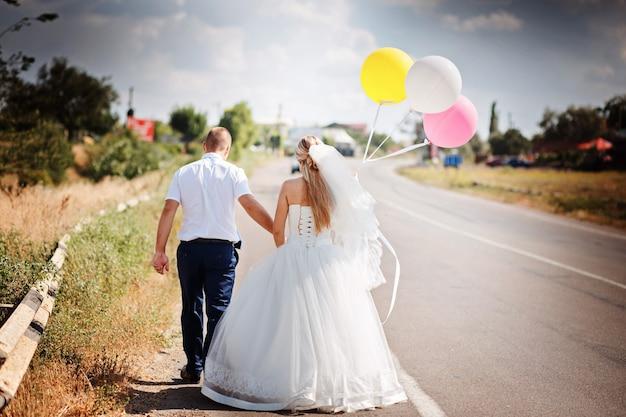 Noiva e noivo com balões caminhando juntos na estrada