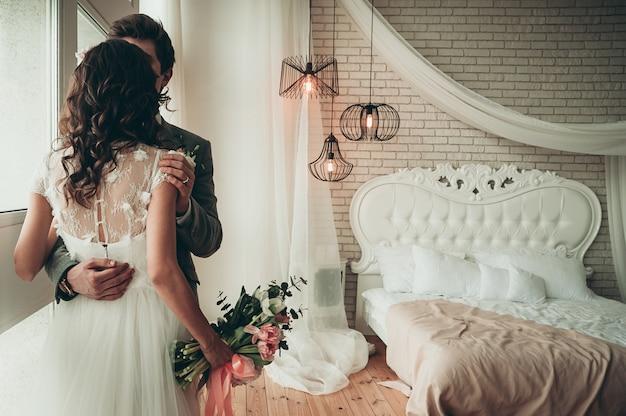 Noiva e noivo com um buquê de casamento em pé junto à janela