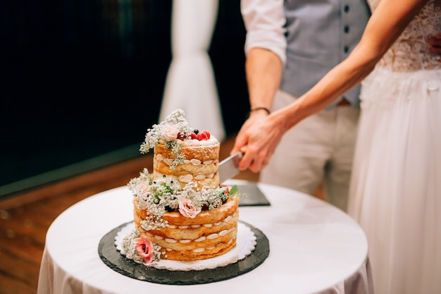 Noiva e noivo cortam juntos um bolo de casamento de duas camadas decorado com flores e frutos silvestres em um