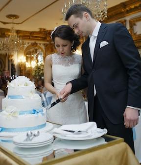 Noiva e noivo cortam o bolo
