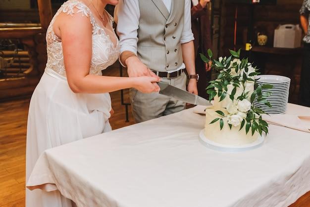 Noiva e noivo cortando lindo bolo de casamento decorado com folhas
