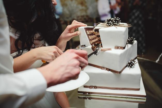 Noiva e noivo cortar o delicioso bolo de casamento