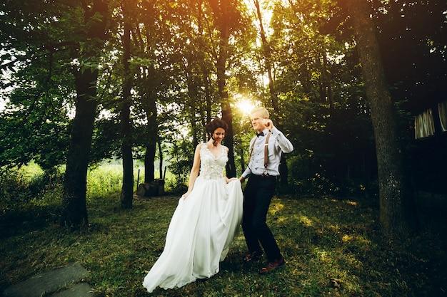 Noiva e noivo dançando na natureza, em algum lugar da floresta