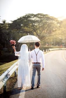 Noiva e noivo de mãos dadas com guarda-chuva e caminhando juntos
