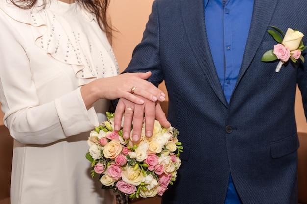 Noiva e noivo de mãos dadas, mostrando seus anéis casal de noivos segurando buquê