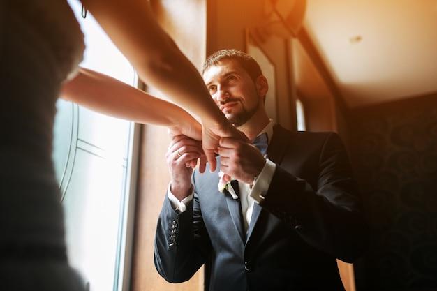Noiva e noivo de mãos dadas na janela de um restaurante
