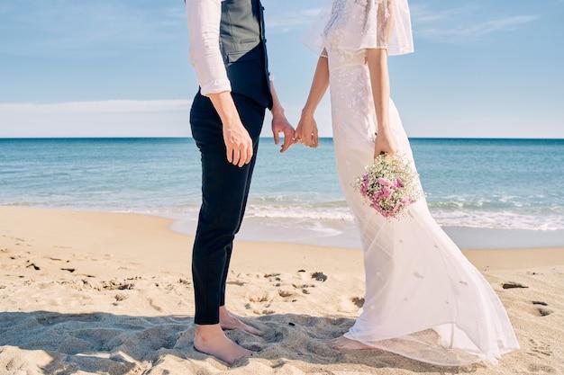 Noiva e noivo de mãos dadas na praia em vestidos de noiva