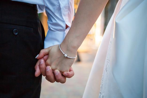 Noiva e noivo de mãos dadas no dia do casamento
