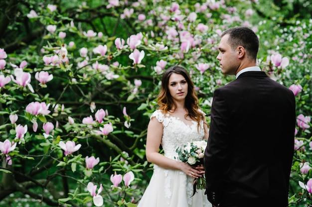 Noiva e noivo elegantes perto da árvore de magnólia.