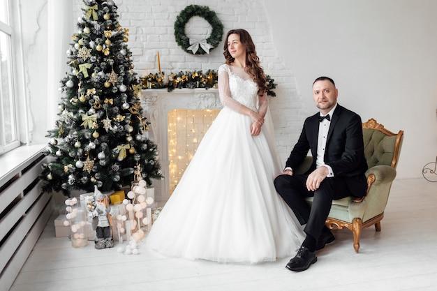 Noiva e noivo em estúdio em fundo decorado com árvore de natal no dia do casamento