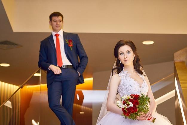 Noiva e noivo em pé na escada
