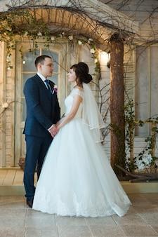 Noiva e noivo em roupas de casamento se abraçam em casa. casal apaixonado após cerimônia de casamento
