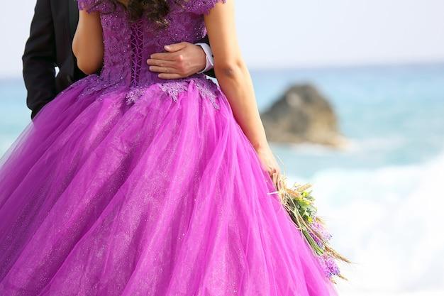 Noiva e noivo em roupas elegantes na praia