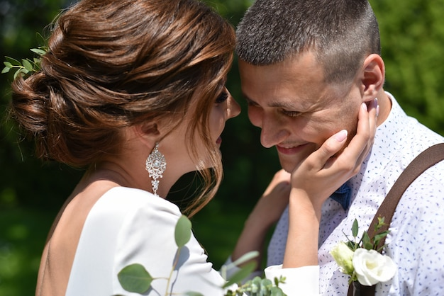 Noiva e noivo em um beijo de buquê em um parque verde