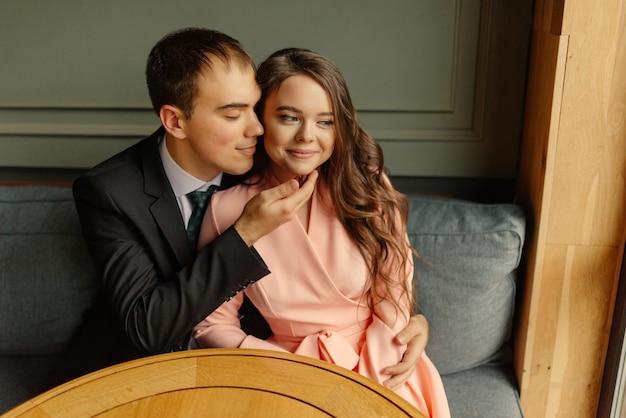 Noiva e noivo em um café. marido e mulher dão as mãos. noivo beijando uma noiva. linda noiva e noivo elegante. casamento.