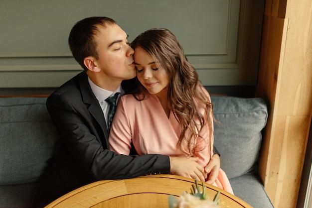 Noiva e noivo em um café. marido e mulher dão as mãos. noivo beijando uma noiva na cabeça. linda noiva e noivo elegante. casamento.