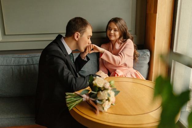 Noiva e noivo em um café. marido e mulher dão as mãos.