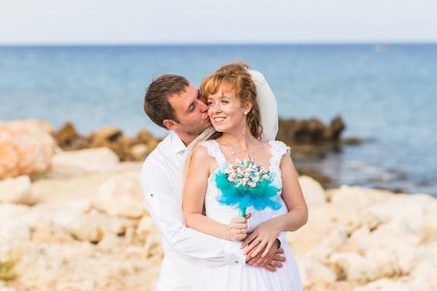 Noiva e noivo em um momento romântico perto do mar