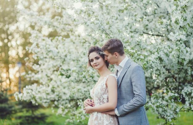 Noiva e noivo em um parque beijando.