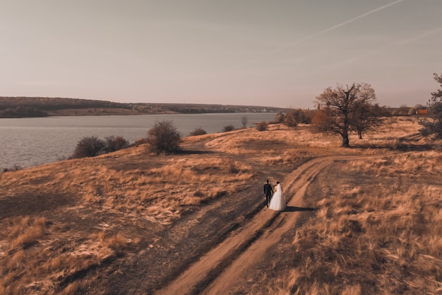 Noiva e noivo em vestidos de noiva caminham ao longo do campo vermelho de outono perto do rio