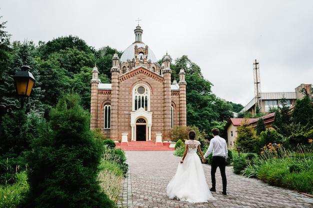 Noiva e noivo entrando na igreja. grande casamento na grande igreja.