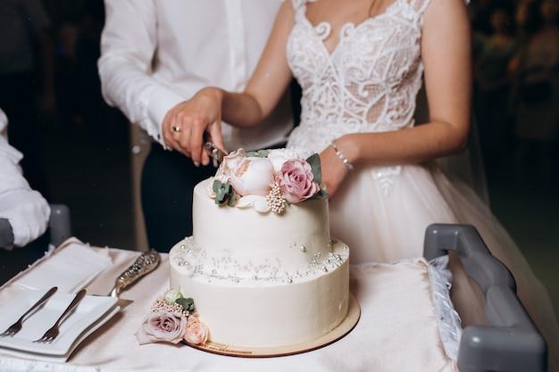 Noiva e noivo estão cortando decorado com flores, bolo de casamento