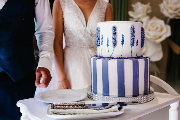 Noiva e noivo estão cortando seu bolo de casamento rústico em banquete.