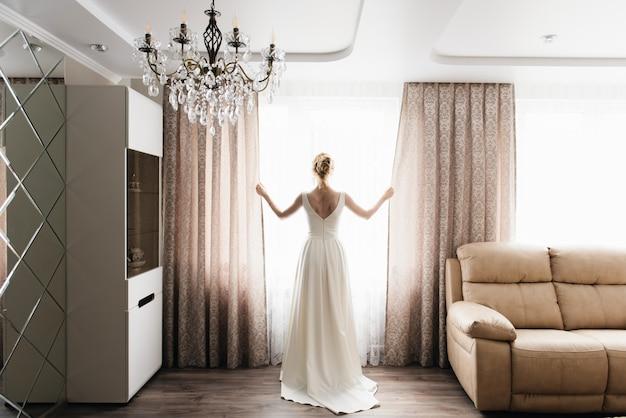Noiva e noivo estão de pé contra a janela, olhando para fora