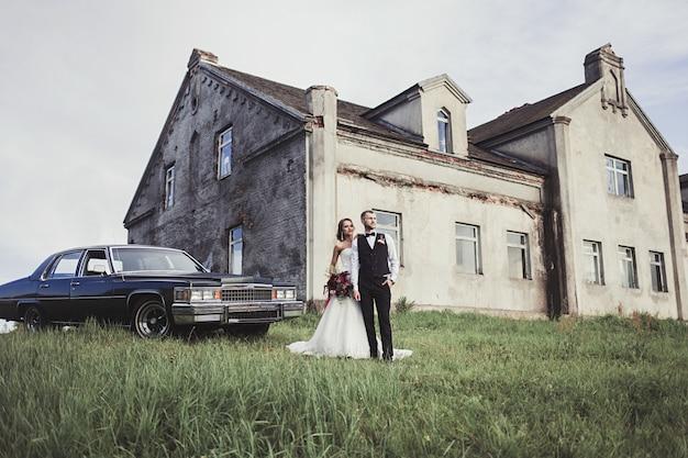 Noiva e noivo estão de pé em uma antiga propriedade