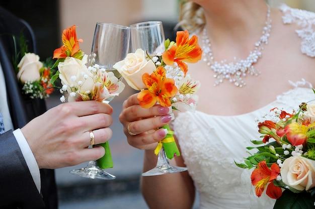 Noiva e noivo estão segurando copos de champanhe