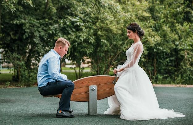 Noiva e noivo estão sentados em um balanço em um dia ensolarado no parque