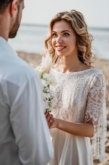 Noiva e noivo fazendo um casamento na praia