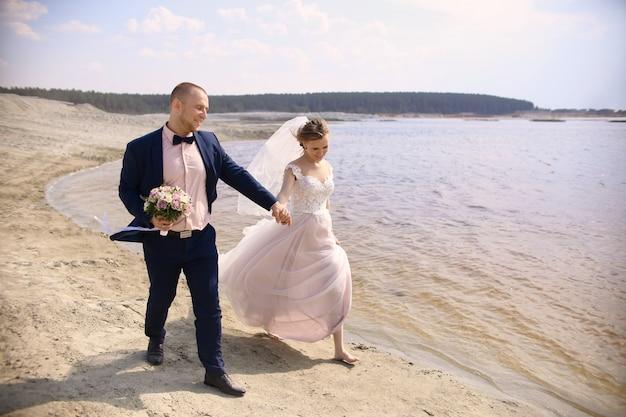Noiva e noivo felizes correndo ao longo do lago da costa