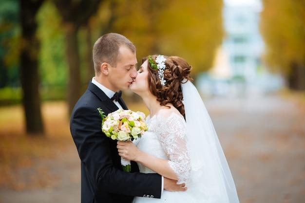 Noiva e noivo felizes em seu casamento abraçando
