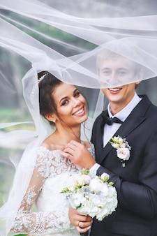 Noiva e noivo felizes em um parque abraçando sob o véu. casal de noivos apaixonados